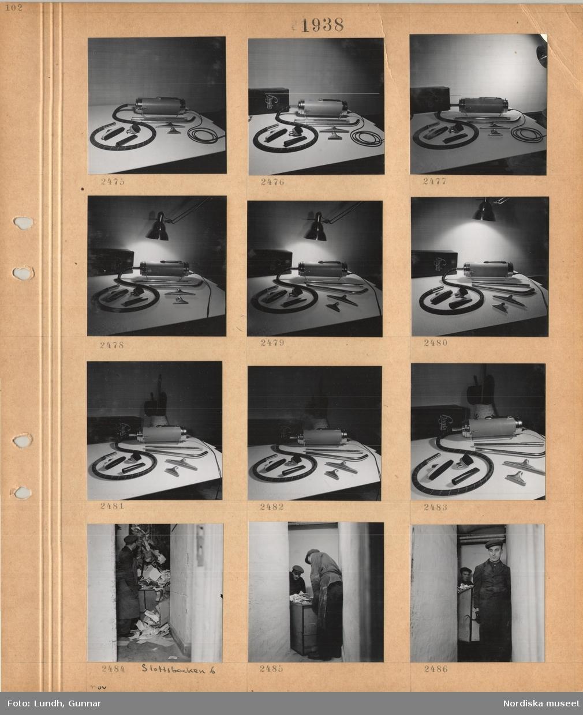 """Motiv: En dammsugare med olika tillbehör upplagd på ett bord, låda med lock märkt """"Hugin"""", lampa, man i arbetskläder i soprum, Slottsbacken 6, två män bär ut en sopbehållare i trångt utrymme."""