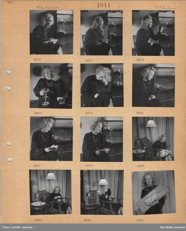 Motiv: Stockholm, modell i klänning som poserar, sitter och läser vid en skrivbyrå med tänd ljusstake, håller i en ljusstake, sitter i en fåtölj bredvid bord med fruktfat, håller i en tekopp, håller i en bok, taklampa, står med inslagna julpaket i famnen.