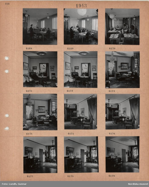 Motiv: Interiör läsesal eller arbetsrum, kvinnor sitter vid bord med arkivmappar, spiraltrappa, rum med bord fulla med handlingar, hyllor längs väggarna, kvinnor och män arbetar, interiör av rum i sektioner, bord, stolar, skrivbyrå, tavlor, soffa, takbelysning, draperi, mattor, skåp, krukväxt.