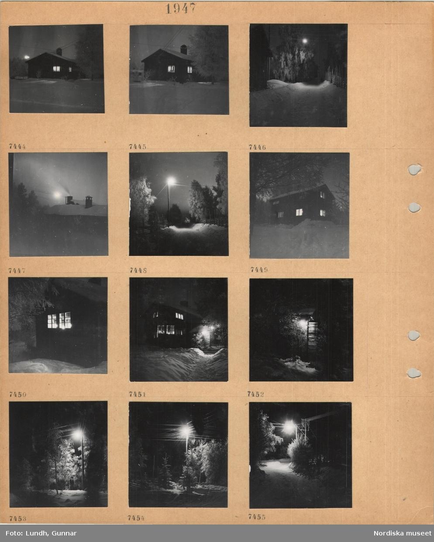 Motiv: Tällberg, bostadshus i snö, snö på träd, väg, trägärdsgård, skorstenar, gatlykta, upplysta fönster i hus, telefonstolpe.