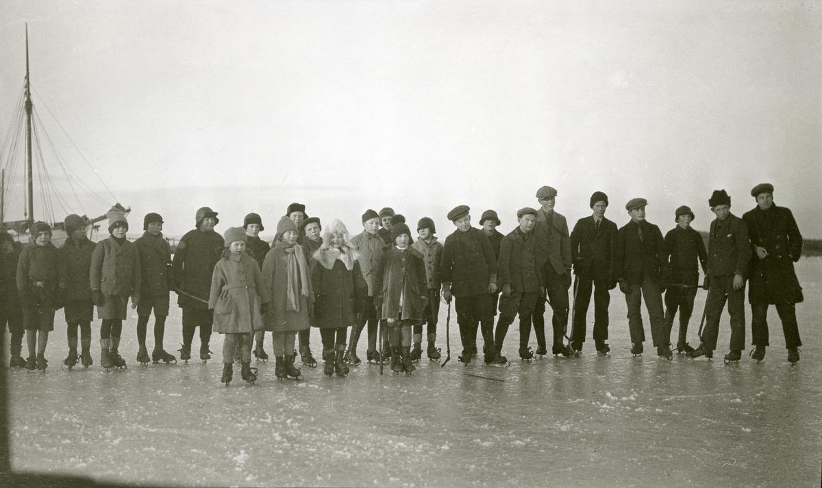 """""""Skokk"""" med unger stående på isen med skøyter på bena i Fredriksvern (Stavern). Fiskeskøyte (el. lign.) skimtes i bakgrunnen til venstre."""