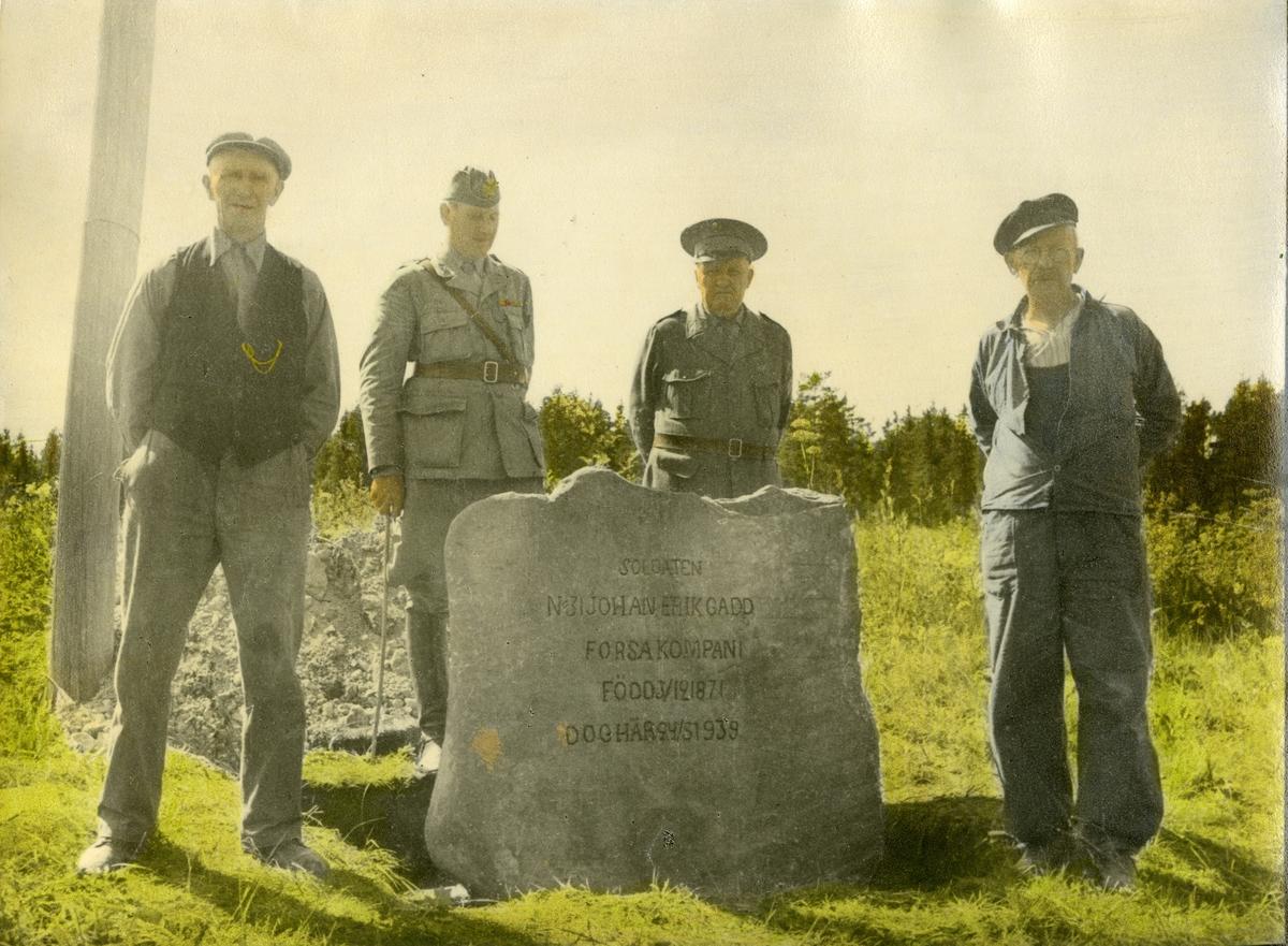 Grupporträtt av fyra män vid minnessten över soldat från Hälsinge regemente I 14.