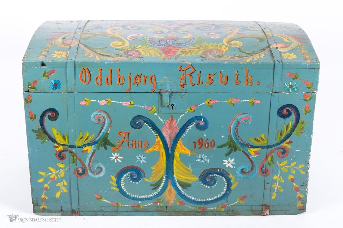 Kista har blågrå bunnfarge og er dekorert med enkel, amatørmessig rosemaling. Akantus, ranker og blomster.