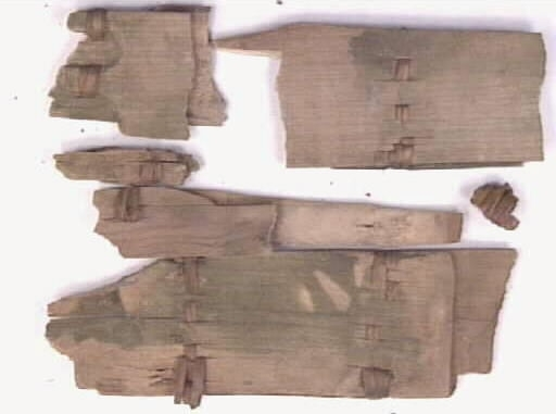 Delar av en svepask. Svepaskens lock och botten är intakta medan svepet är fragmentariskt. Bottnen, locket och svepet har varit sammanfogade med sex stycken rottåger. Svepet är profilerat och har varit sammanfogat med släta stygn. På lockets ovansida är bokstäverna H T inristade.