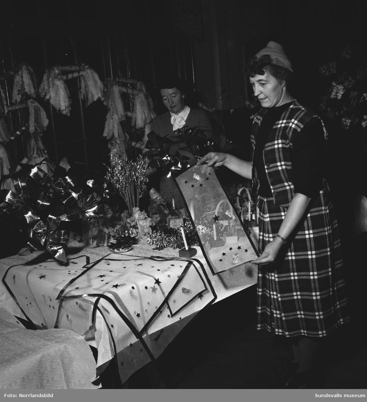 Julmässa i Skönsberg, två damer visar upp juldekorationer till försäljning.