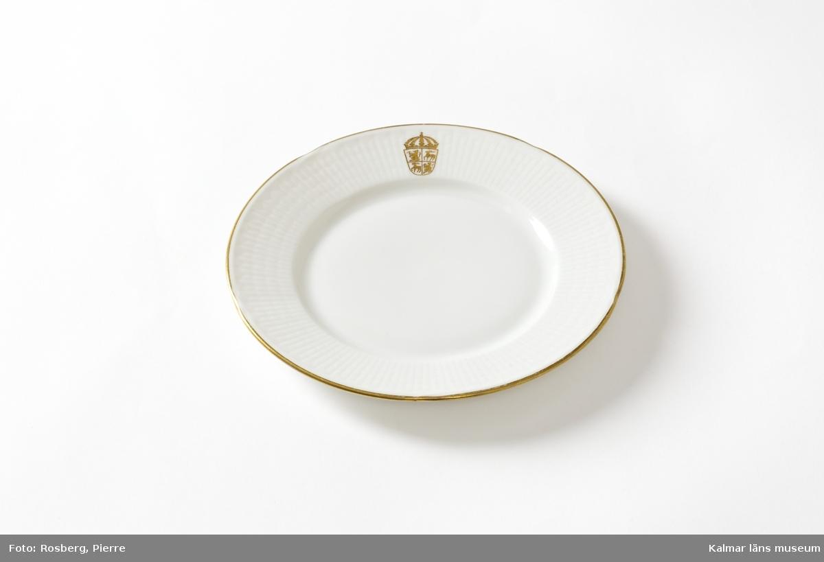 """KLM 44717:4 Assiett, av porslin. Dekoren består av en axliknande relief. Residensets servis är i vitt porslin, dekorerad med länsvapnet i guld samt en guldkant. Porslinet är tillverkat av Rörstrand. Modellen heter """"Nationalservisen"""" och är formgiven av Louise Adelborg för Stockholmsutställningen 1930. Stilen är 1920-tals klassicism. Servisen blev mycket populär och tillverkades fortfarande 2013."""