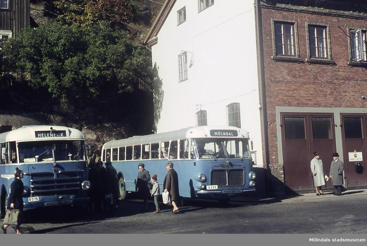 Två blå bussar står på en busshållplats vid Gamla Torget i Mölndal, 1970-tal. Kv 45:21. Huset till höger är Kvarnbygatan 41, som tidigare var brandstation och garage för polisbilar, numera Mölndals målarskola.