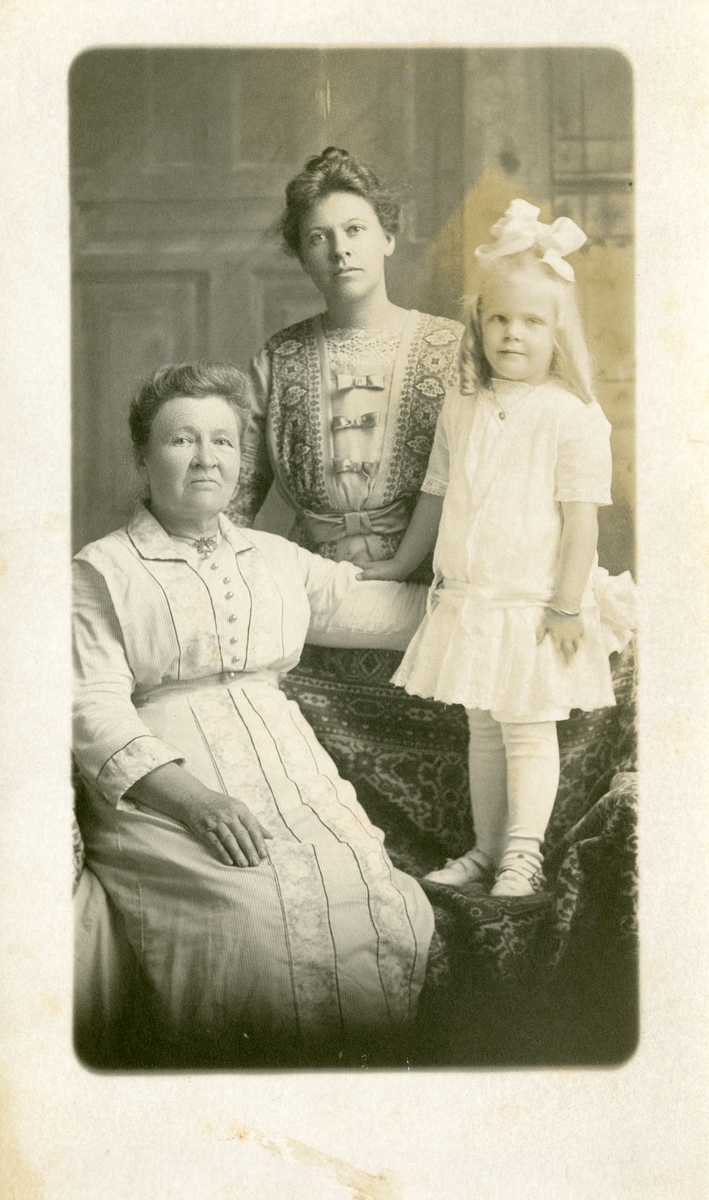 Prospektkort av ei lita jente saman med to kvinner.