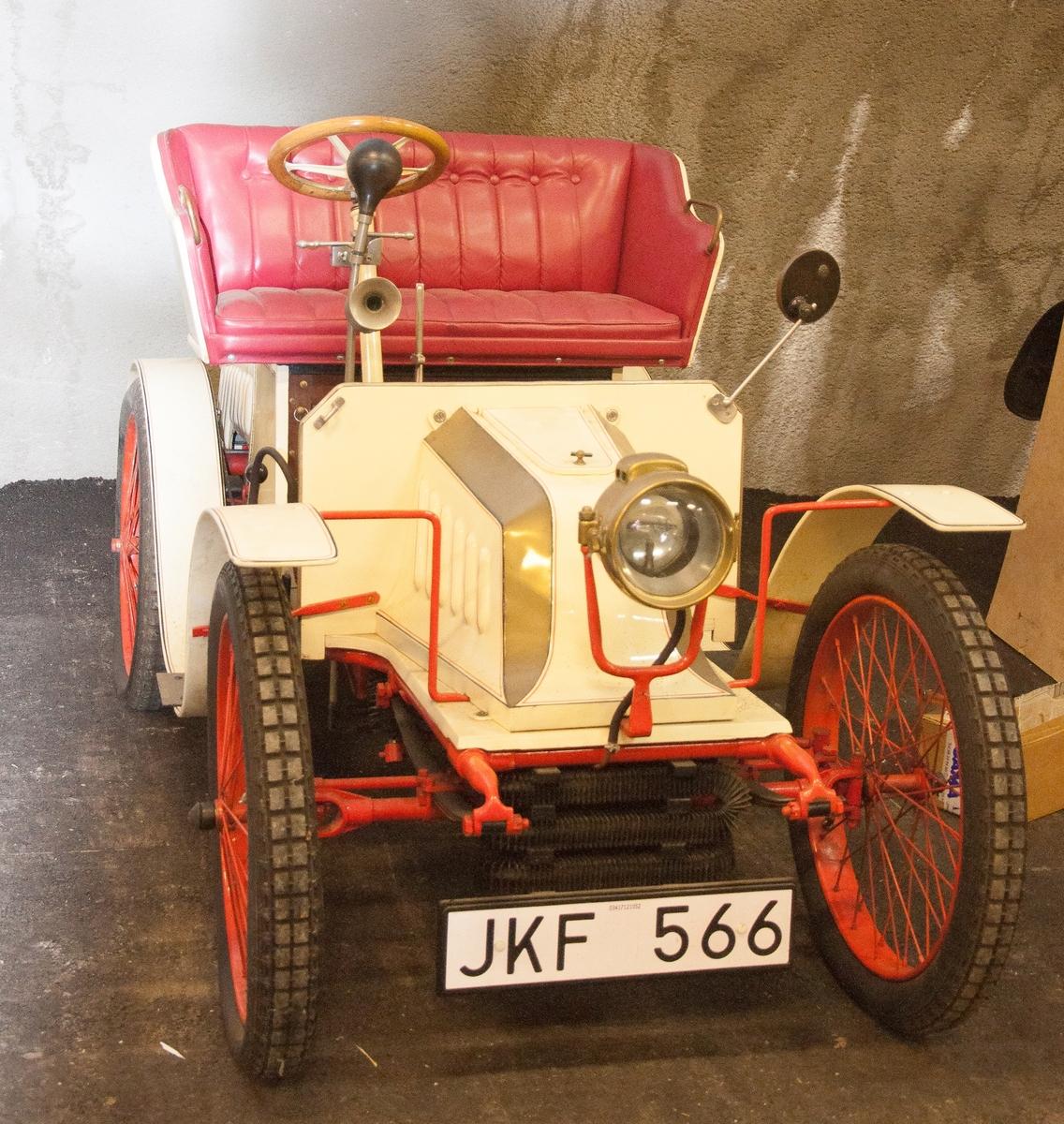 Tvåsitsig personbil. Fordonet var ursprungligen en Quadricycle av fabrikat De Dion årgång 1898. Karossen är påbyggd av tillverkaren Bailleau. Brittisk registreringsskylt AC494. JKF566 i bilregistret. Tillbehör: Vev och diverse lösa delar(50st)