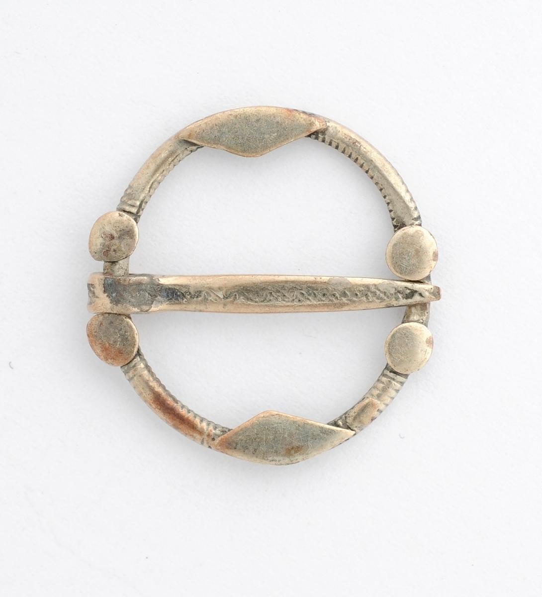 Barnesølje, Rund, støypt ring i sølv (manglar stempel). Pålodda fire små flate rundingar, og to rombe liknande plater. Laus tann.
