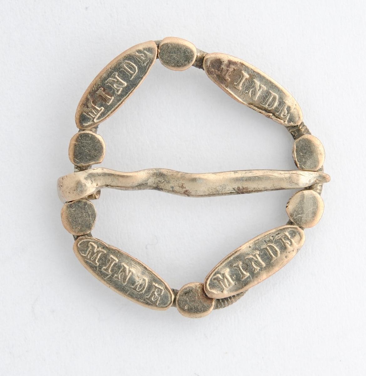 Sølje, halsring i sølv. Støypt ring med innstøypt MINDE på fire pålodda plater på framsida. Laus tann med stempel O H 23 (?) på baksida.
