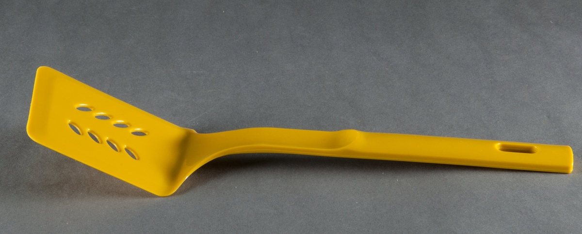 """Stekspade, gjuten i gul plast. Modell """"Gourmet Plastic"""". Rektangulärt blad med åtta ovala hål, ställda diagonalt i två rader. Design Gunnar Cyrén. Tillverkad i Japan för Dansk Designs Ltd, USA."""