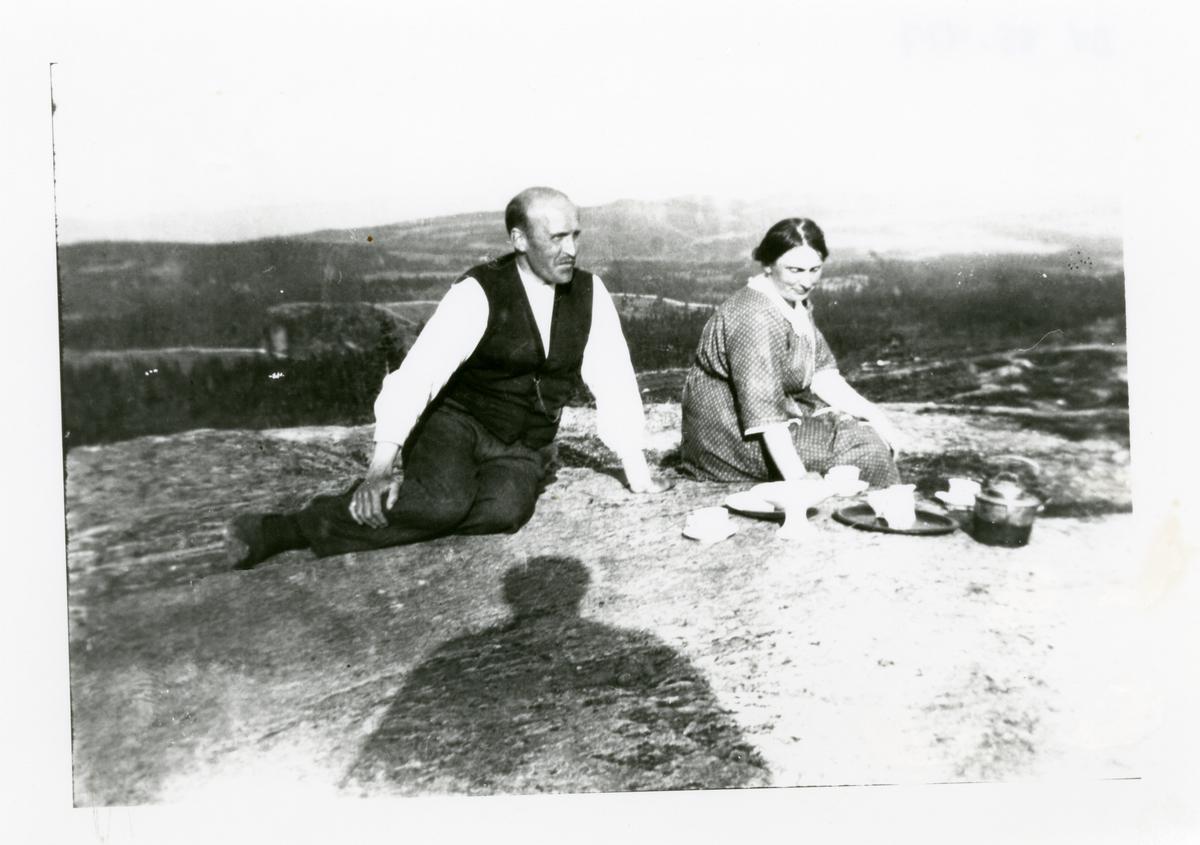 Kvinne og en mann har kaffepause på fjellet. De har dekket på en fjellknaus.