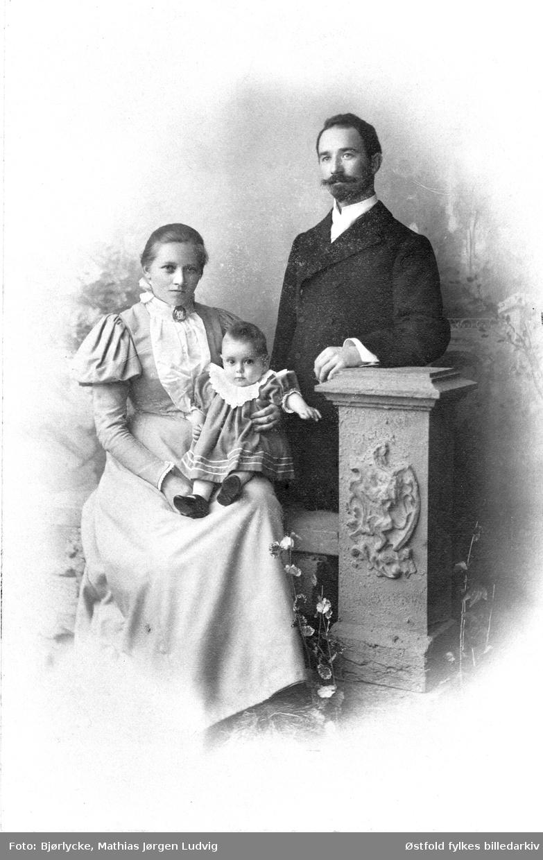 Portrett i kabinettformat tatt i atelier av ukjent kvinne og mann med barn, ca. 1897- 1902.