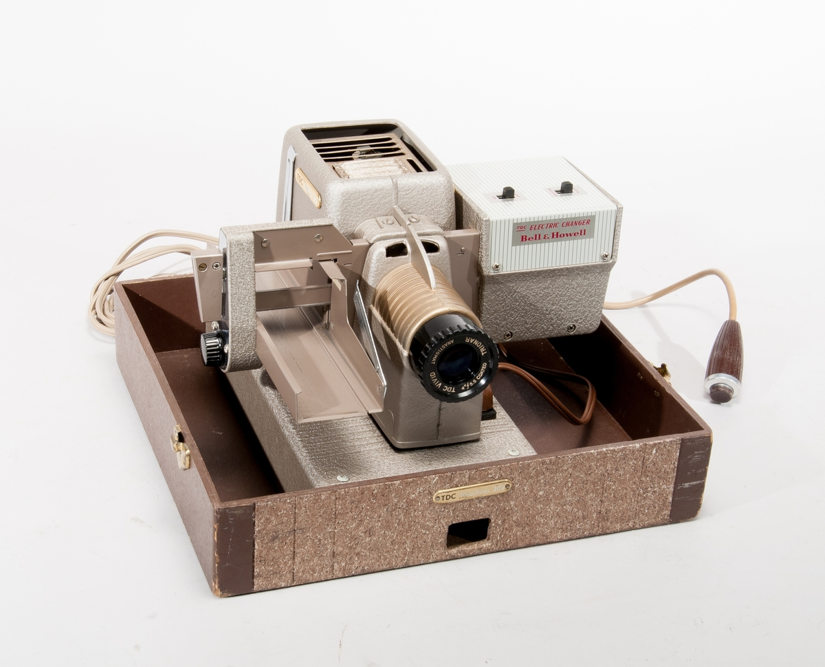"""Småbildsprojektor för visning av diabilder. Fabrikat Bell & Howell, modell """"Headliner 303"""" utrustad med """"Electric Changer"""", en mekanism för automatisk frammatning av bilder i rakt magasin. I ursprunglig förvaringsbox som tillsluts med tre hasplås. Tillbehör: elkablar, sladd för fjärrmanövrering."""