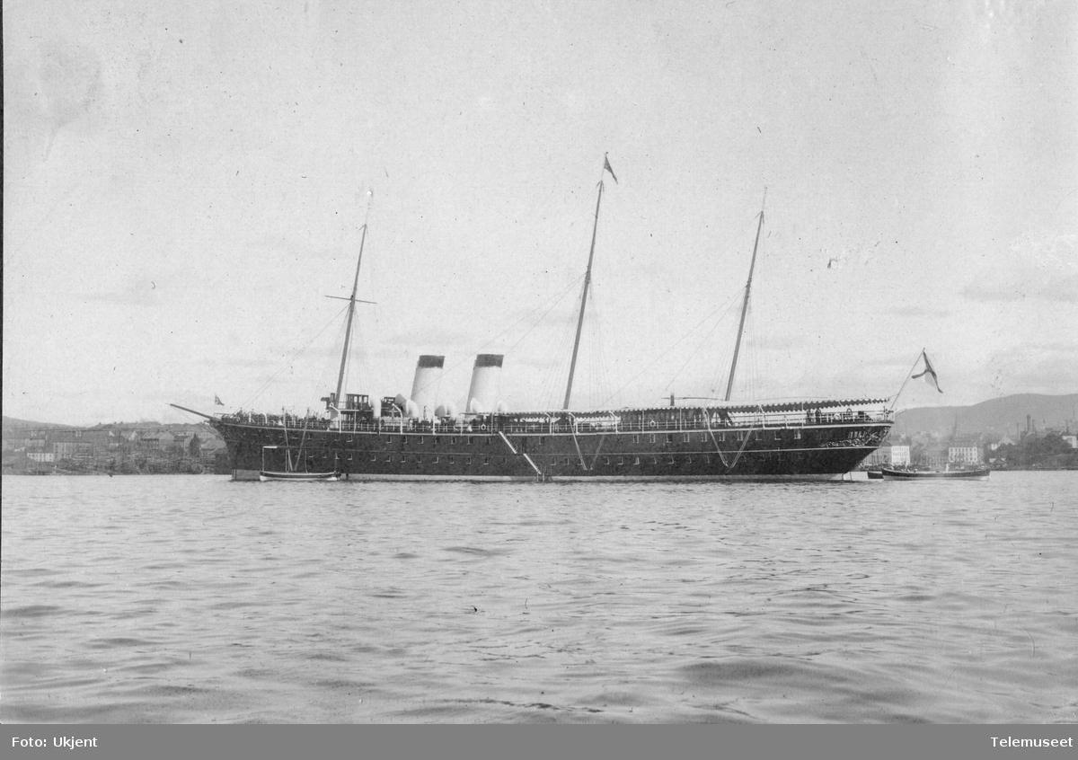 Dampskip med to skorsteiner, tre master, klyverbom og engelsk flagg i Kristianiafjorden utenfor Akers mekaniske værksted