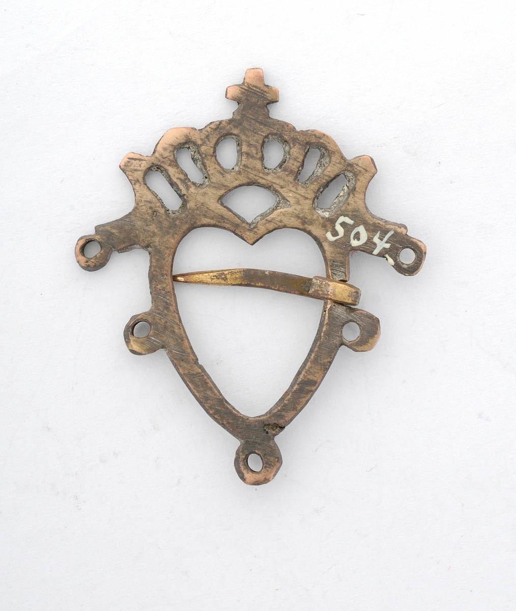 """Sølje, hjartesølje støypt i messing, forma som eit hjarte med ei """"krone"""" øverst. Enkel dekor, delvis gjennombroten. Fem ringar. Smidd tann (nål). Glatt bakside."""