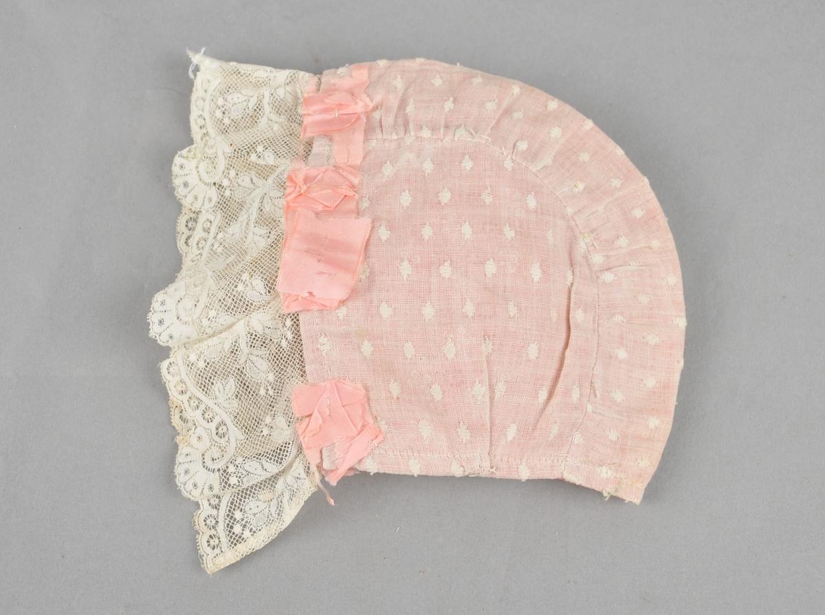 Dåpsluve i kvit tynn linlerret med påbroderte romber. Fora med rosa bomullstøy med trykte små roser i mørkare rosa og kvitt.  På framkanten er det påsett ei kvit blonde.  På delar av framkanten sit restar etter rosa silkeband. Luva har midtstykke og to sidestykker. Maskinsydd.