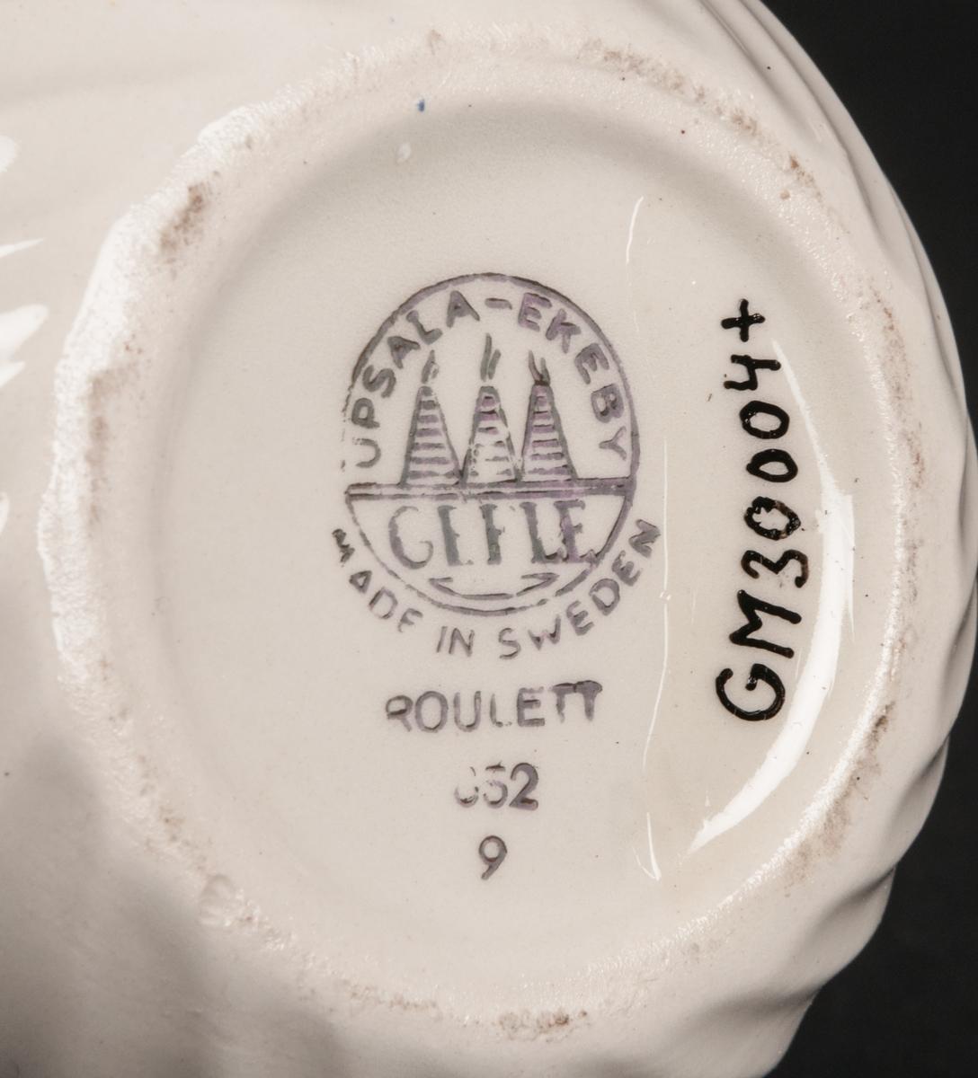 """Sockerskål med lock, flintgods, tillverkad vid Gefle Porslin. Modell: """"Roulett"""". Vitglaserad, närmast klotformad med vertikalt bågmönster. Lockets knopp klotformad med förgylld topp. Färgstämpel i grått: Upsala-Ekeby Gefle och rundugnar i cirkel, Made in Sweden, Roulett 852 9."""