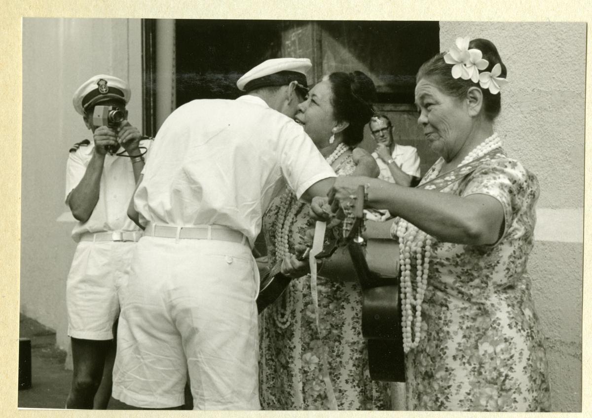 Bilden föreställer en besättningsmedlem i vit sommaruniform som kramar om en kvinna. I bakgrunden syns ytterligare en besättningman som fotograferar händelsen. Bilden är tagen i samband med minfartyget Älvsnabbens långresa 1966-1967.