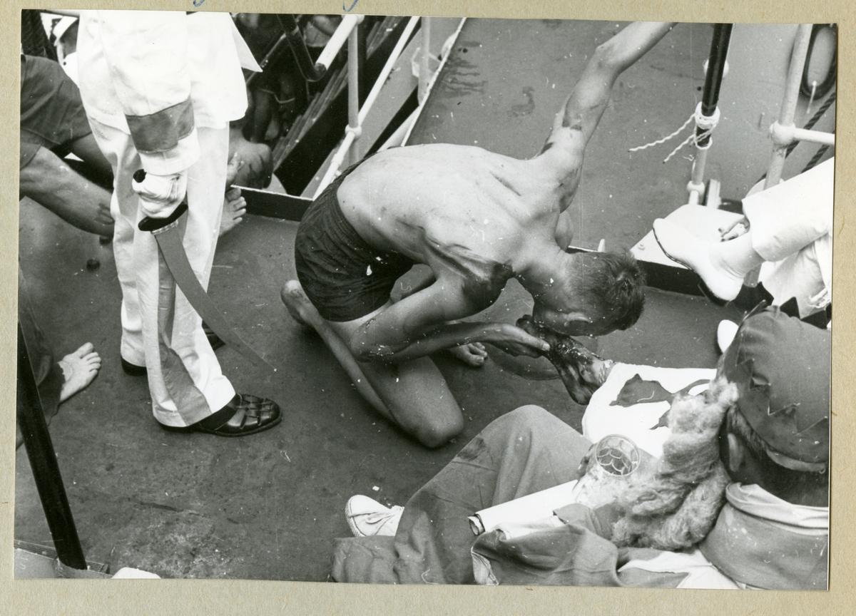 Bilden föreställer en barbröstad besättningsman ombord på minfartyget Älvsnabben som håller på att genomgå ett linjedop och får kyssa kung Neptuns fot. Bilden är tagen under fartygets långresa 1966-1967.