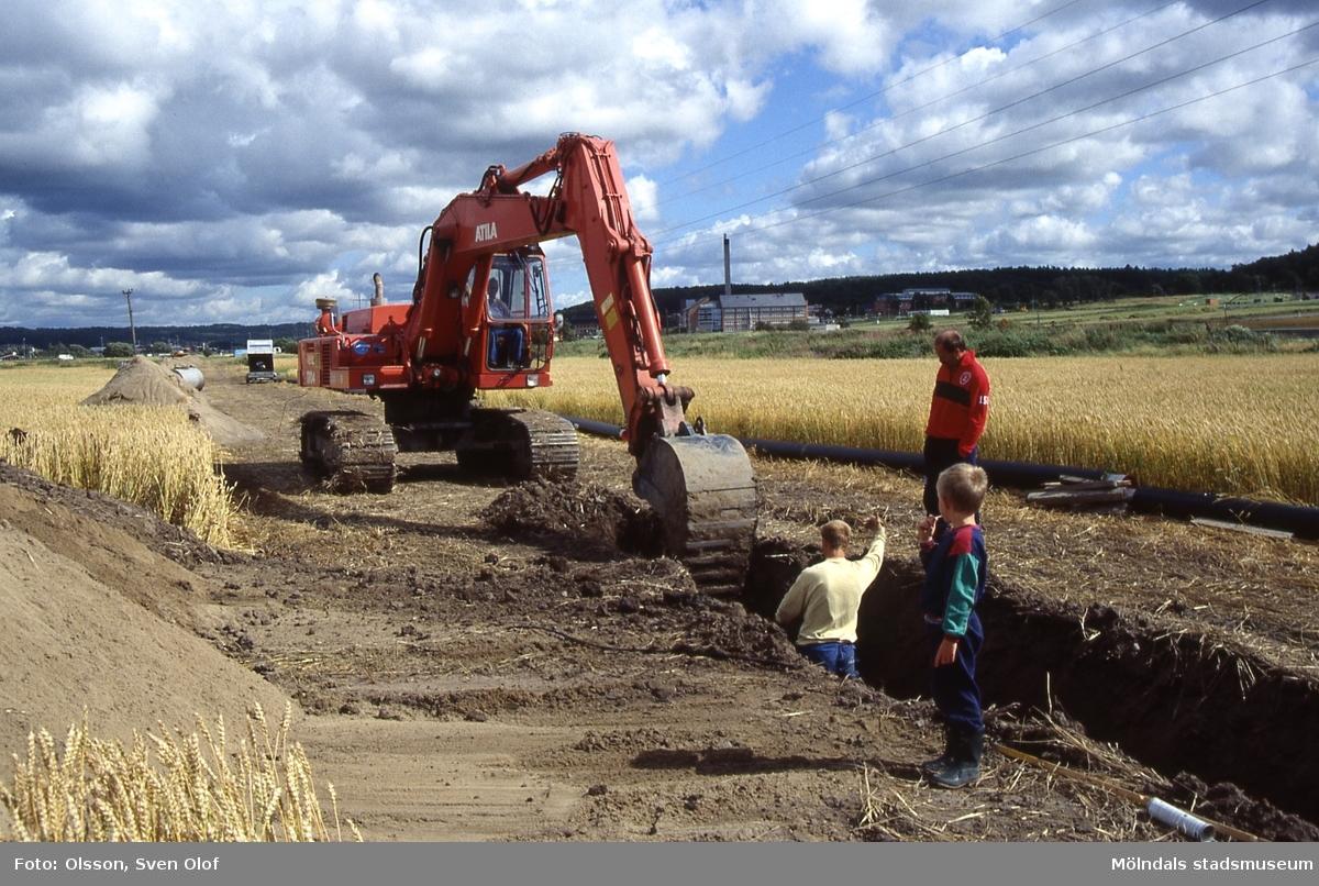Mellangården 1 i Fässberg, Mölndal, i augusti 1991. Pripps vattenledning från Kallebäck läggs för tredje gången. I röda tröjan ses Bengt Olsson. Pojken är sonen Samuel. F 6:5.