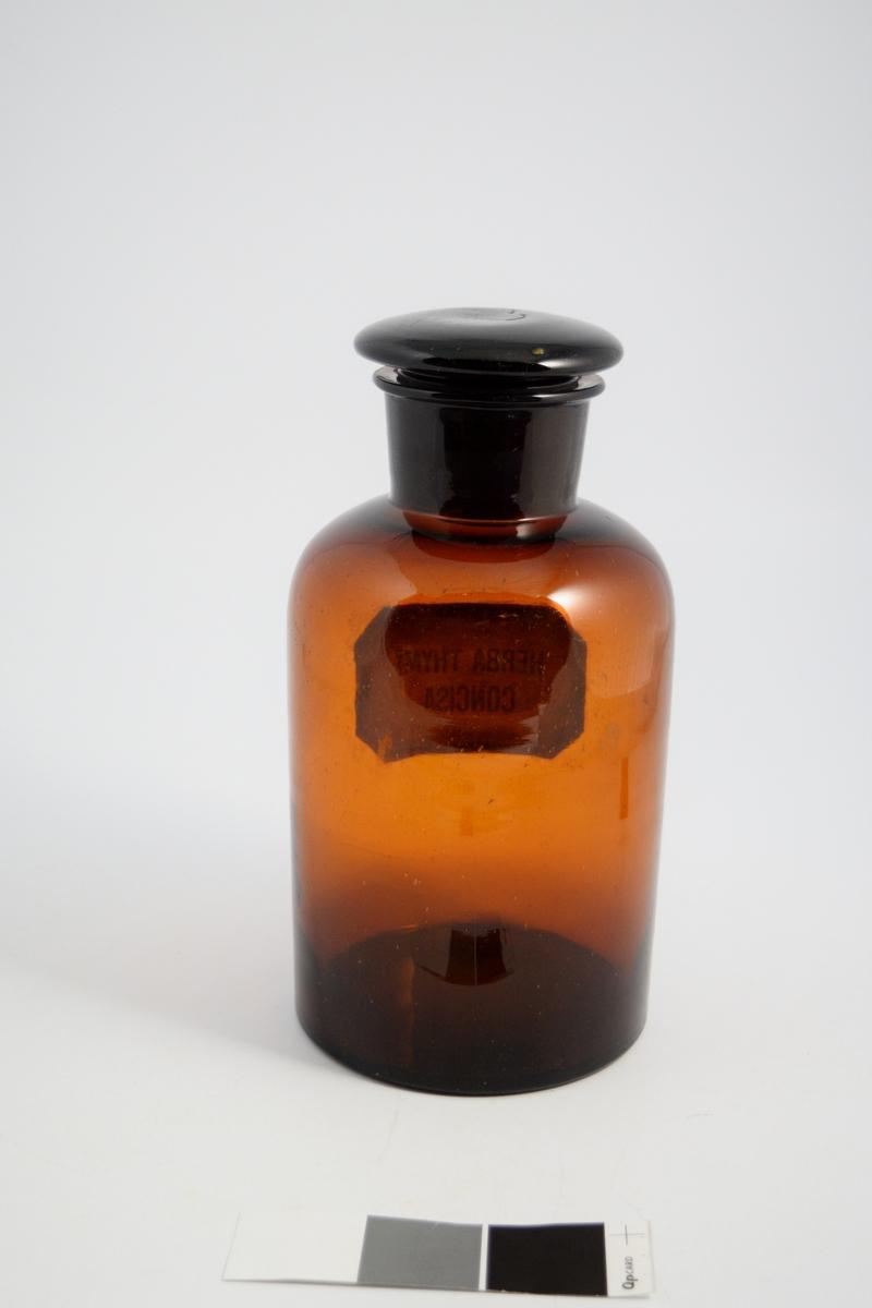 Brun glasskrukke, vid hals, brun glasspropp. Påført hvit etikett med sort ramme og skrift. Herba Thymi Concisa vil si: oppdelt timian. Timian ble brukt i hostesaft.