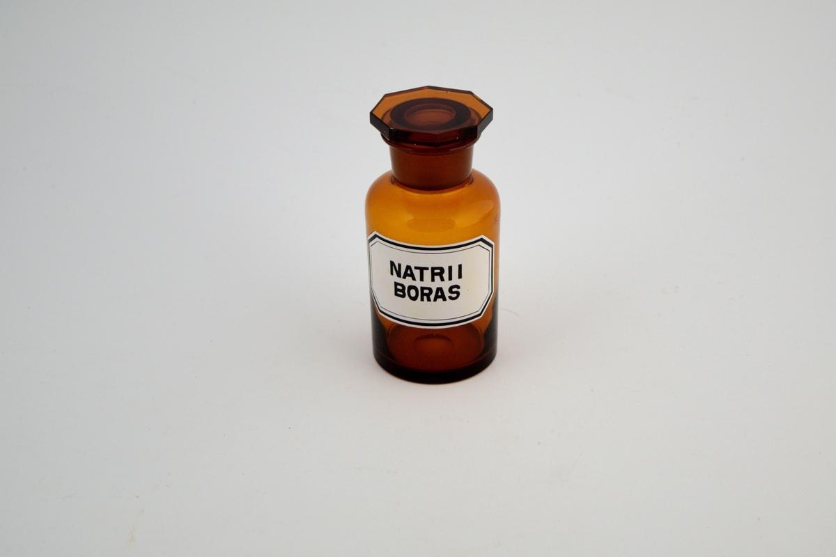 Brun glasskrukke, vid hals, med brun glasspropp. Påført hvit etikett med svart skrift. Glasskukken ble brukt til oppbevaring av pulver. Nartii boras, eller natriumborat, ble brukt mest i salver og i oppløsninger.