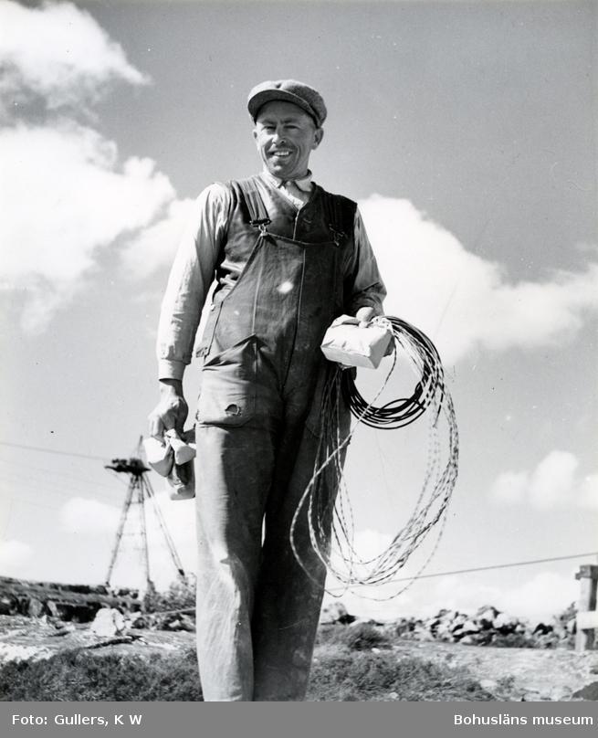 En stenhuggare i hängselbyxor och keps tittar leende in i kameran, han håller metalltrådar och papperspåsar i händerna