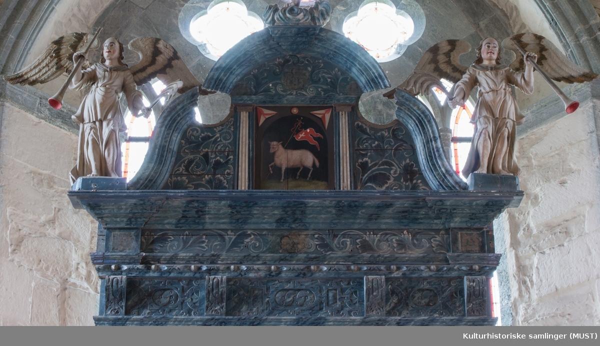 Midtmotivet på altertavlen viser Korsfestelsen, med Maria og Johannes ved foten av korset. På sidene på samme rekke sees billedlige fremstilling av Tro (Fides) og Håp (Spes). På øverste rekke vises en billedlig fremstilling av lammet med seiersfanen i midten. På begge sidene på samme rekke er det skulpturer av engler med palmegrein og trompet. På toppen står en skulptur av Kristus, som har oppstått.  Kilde: http://www.kirkesok.no/kirker/Utstein-klosterkyrkje