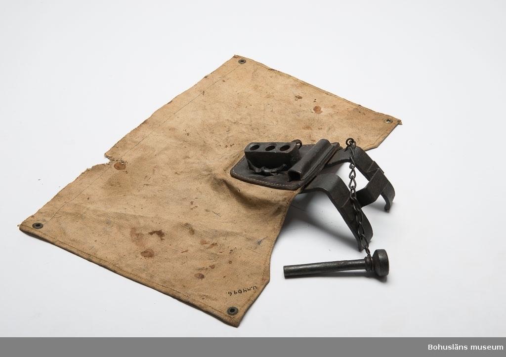 Rektangulärt tygstycke med ett metallskott hål i varje hörn. På ena långsidan är det en järnanordning med en bult som slås in i djurets panna. Bulten kan placeras i tre olika lägen. Tygstycket träs över huvudet på det djur som skall slaktas. Tygstycket är fläckigt och något söndrigt.  Ur handskrivna katalogen 1957-1958: Slaktmask Dukens mått: 57 x 35 cm; bultens L. 14,3 cm. Duken fläckig och något trasig. Rost.  Lappkatalog: 53