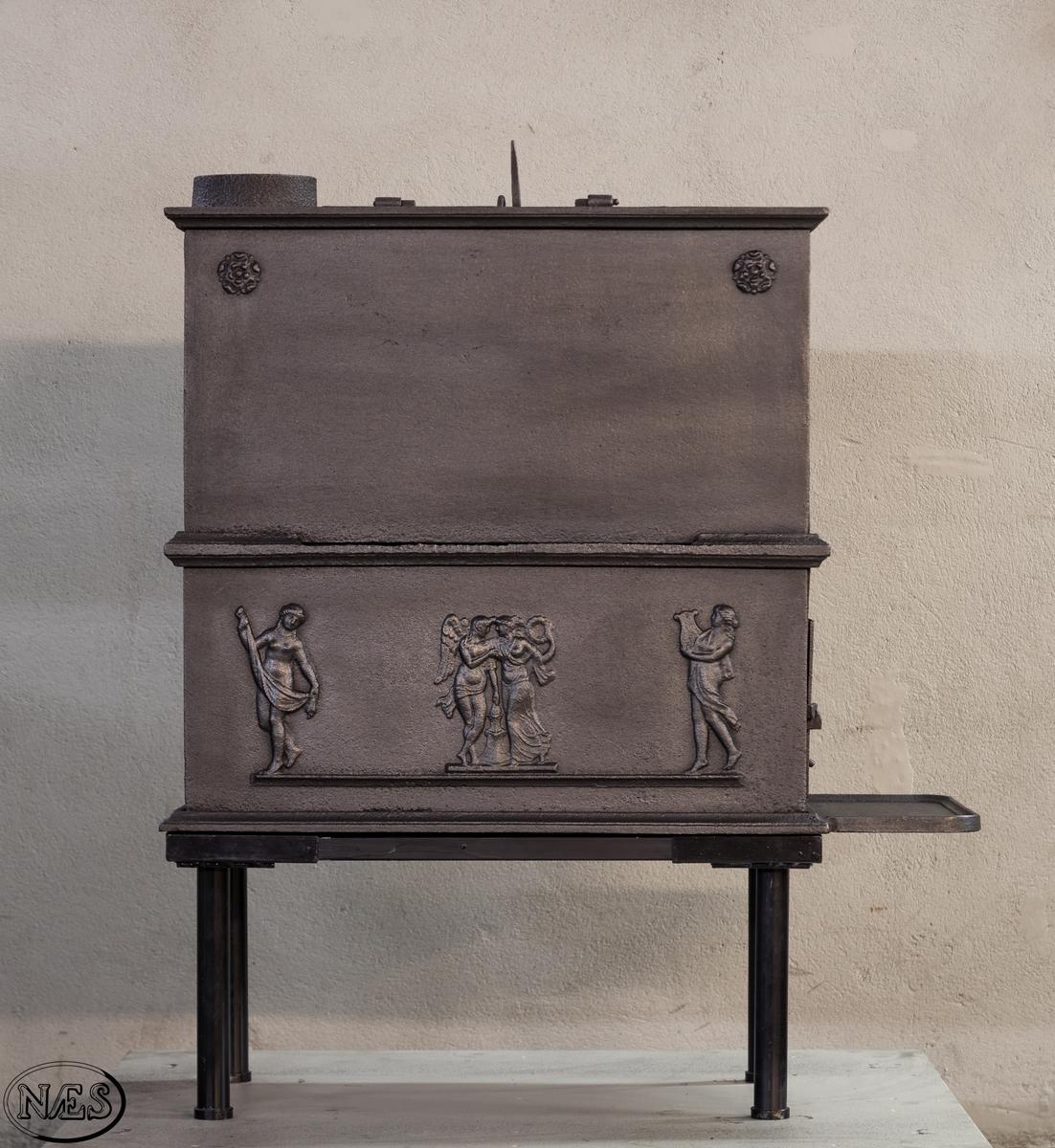 Kokeovn i to etasjer med eget fyrkammer og kokerom. Kokerommet kan åpnes med to dører på langsiden og med en luke i topplaten. Ovnsdøren til fyrkammeret er på kortsiden 1 etg. På langsidene i 1. etg er det tre muser og en engel med lette draperier på en enkel profillist. På kortsidene 2. etg er det draperikledd dansende muse på enkel profillist med en rosett i hvert øvre hjørne. Langsidene i 2.etg er dekorert med en rosett i hvert øvre hjørne.