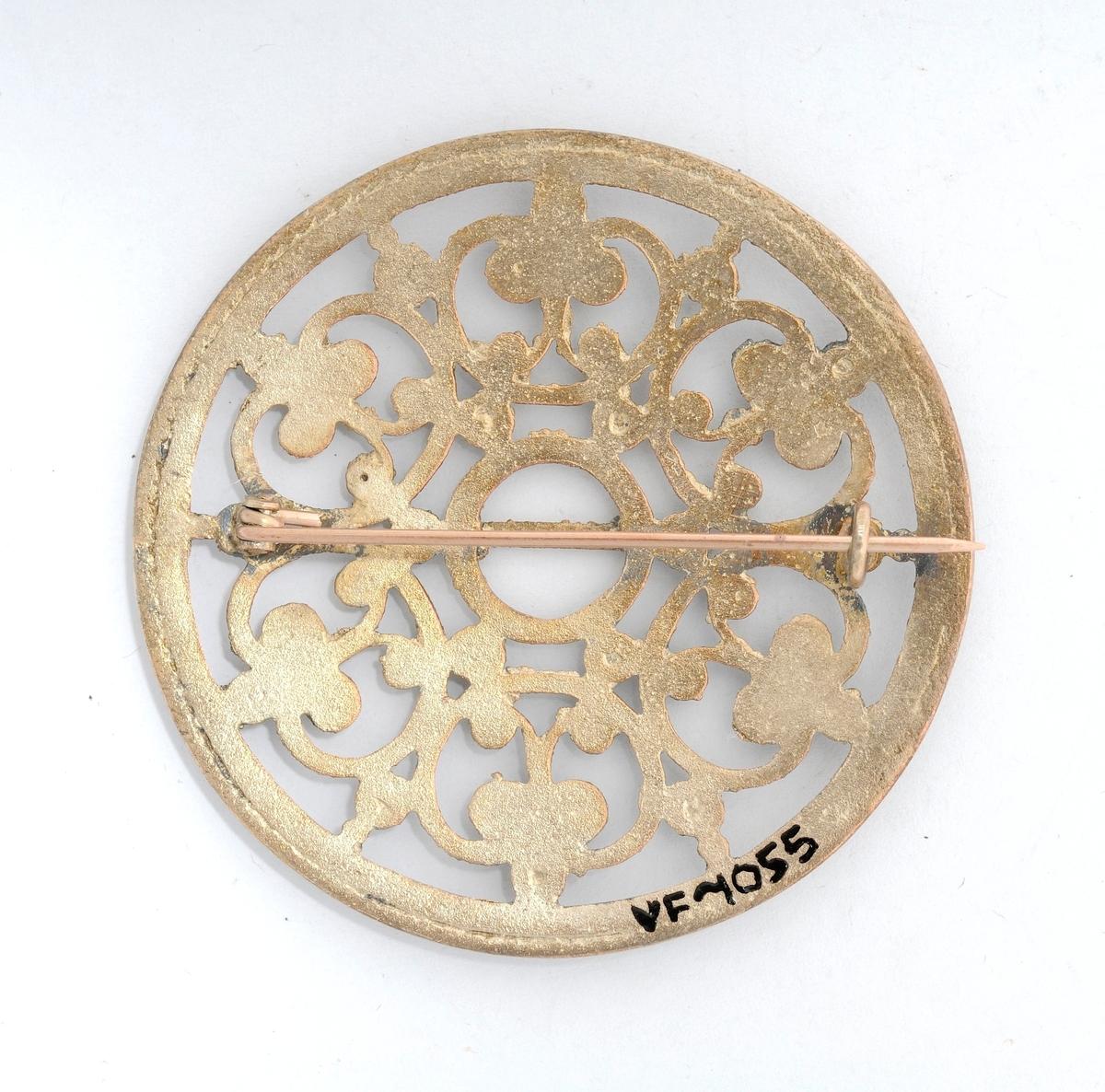 Sølje i sølv (utan stempel), støypt og med mønster på framsida. Tanna er etterlikna etter slik det var på gamle søljer, men fastlodda. Moderne nål på baksida.