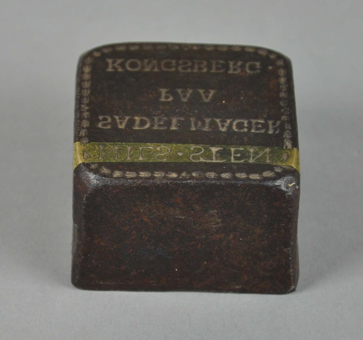 Kvadratisk stempel av tykt jern, med speilvendt innskrift. Det går en gullfarvet stripe langs øverste linje med skrift. Langs kanten av stemplet går det en dekorlinje.