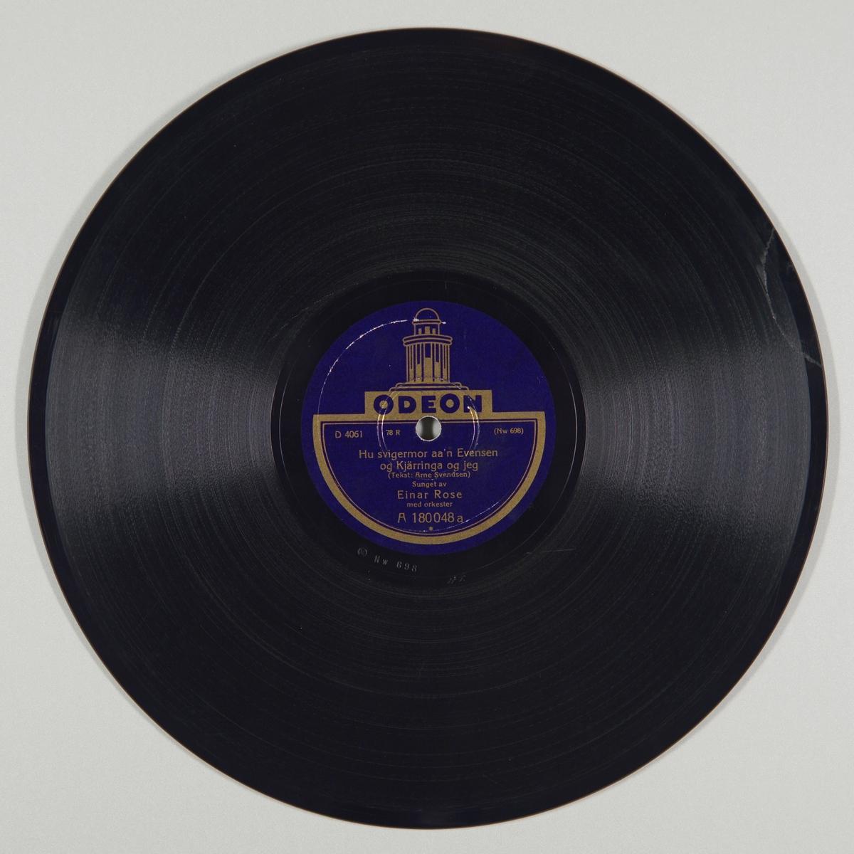 """54280.01: Svart grammofonplate laget av bakelitt og skjellak. Etiketten er mørk lilla med skrift i gull, for tekst se """"Påført tekst/merker"""". På etiketten er det tegning av kuppelen på Odeon. På B-siden er det et lite grønt og hvitt klistremerke på etiketten.  54280.02: Plateomslaget til platen er laget av hvitt papir som er limt. Det er sekundær påskrift på begge sidene, for tekst se """"Påført tekst/merker""""."""