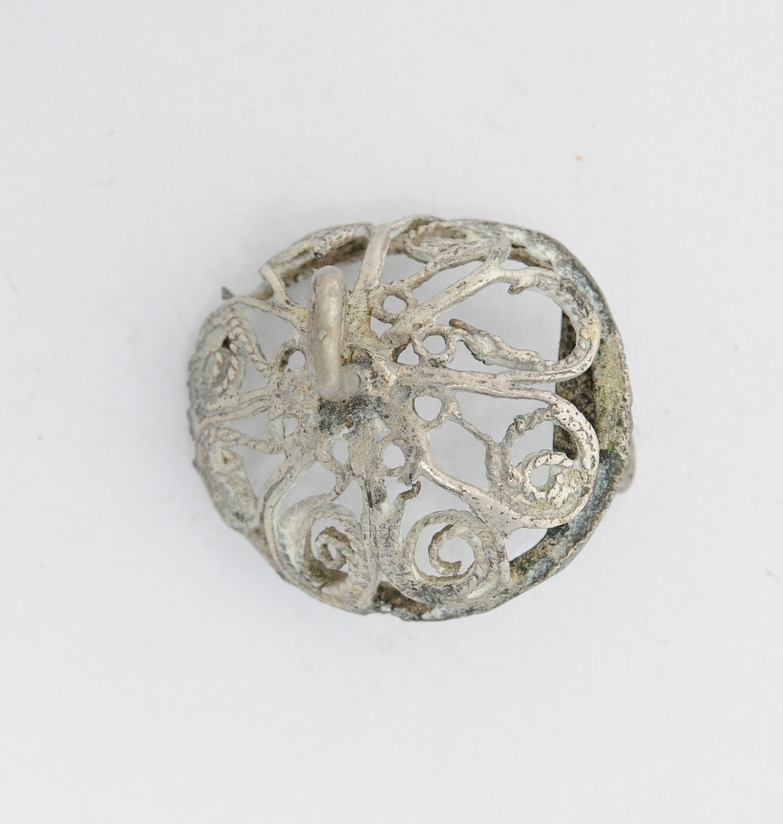 Sølje, halsknapp, i sølv, A og B. Har vore samansett, men er sundbroten i to delar Desse delane er to halvkuleforma knappar i filigransarbeid.  Del A har pålodda krok på baksida, og hempe for vedheng på framsida. Del B har pålodda nål bak, manglar hempe på framsida. Er reparert med tinn eller bly der hempa skulle vore.  Båe er skeive og i dårleg stand.