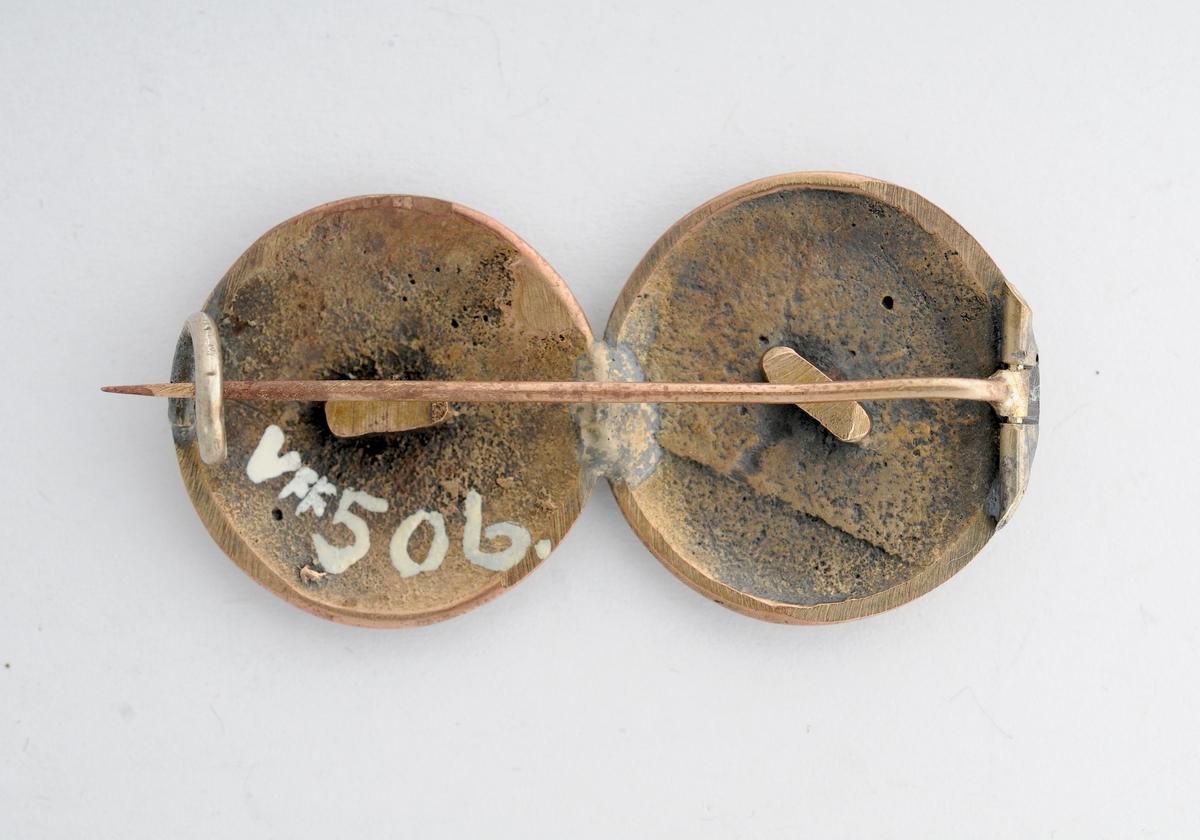 Sølje. Halsknapp i messing. To støypte knappar med ulik dekor på. Sett saman av to knappar, merke etter kramper bak. Pålodda nål og krok på baksida.