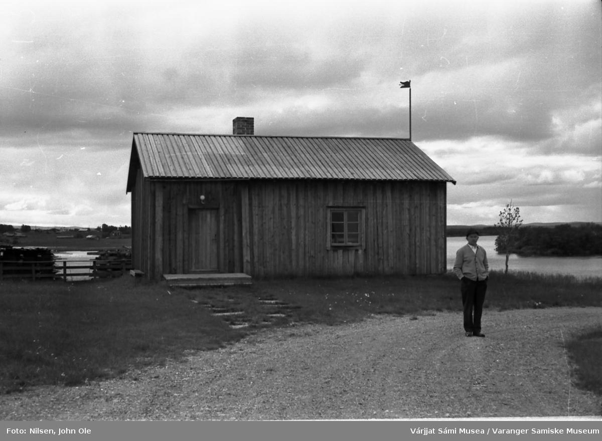 John Ole Nilsen står foran Laestadii Pörte (Læstadius' røykstue) i Karesuando, Sverige. Elva og bebyggelse på finsk side i bakgrunnen. Vei i forgrunnen. 16. juli 1967