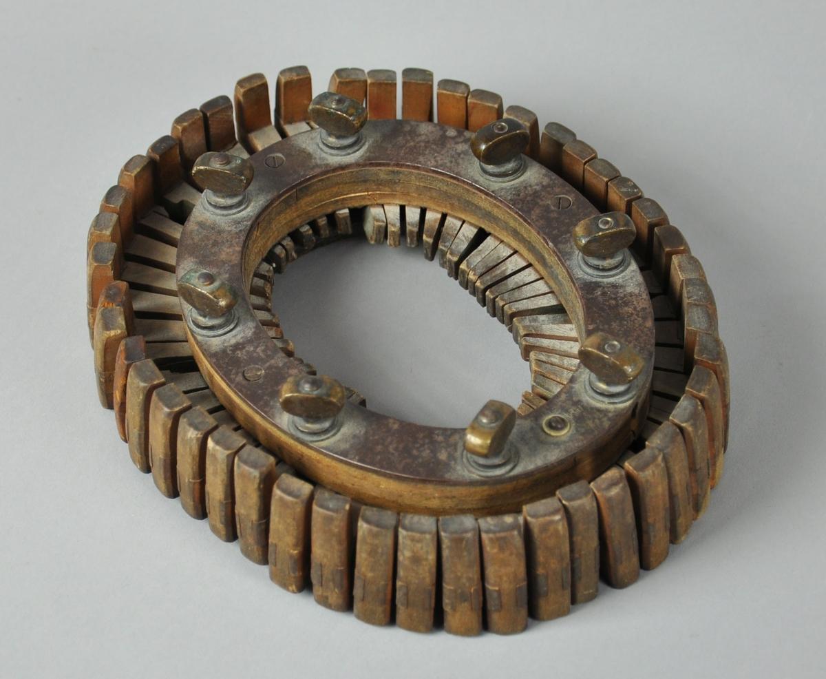Oval gjenstand som består av en ramme med 8 vingemutrer for å regulere 47 målepinner etter hodemål. Pinnene kan gli inn og ut for å utvide og trekke seg sammen for å lage forskjellige former.