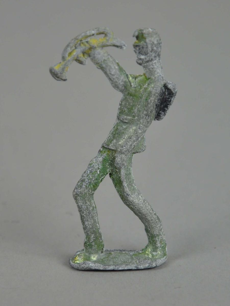 Liten figur av tinn. Figuren er i marsjposisjon på en oval støtte og blåser i trompet.