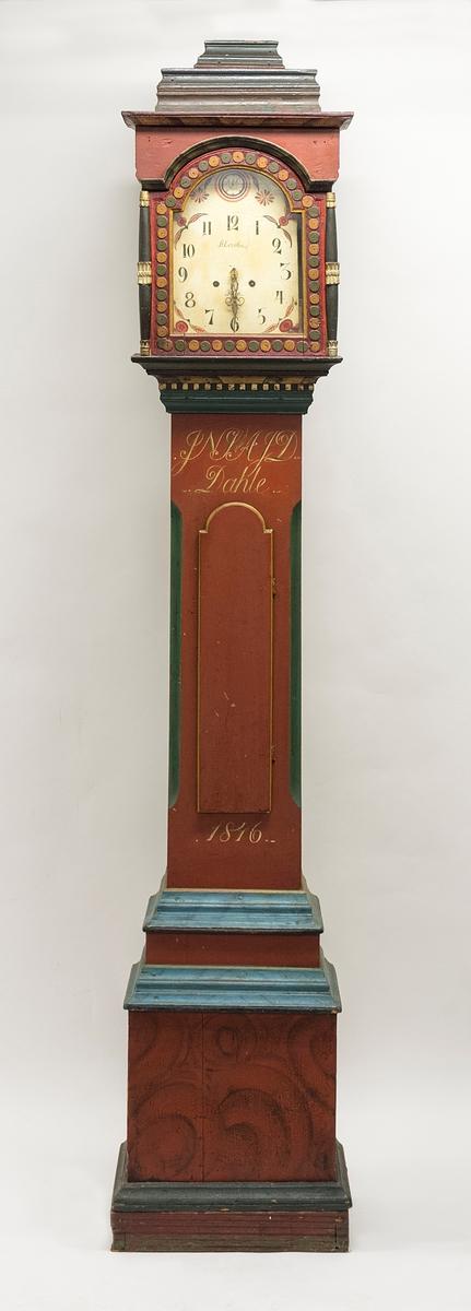 """Klokkeskap produsert i 1816 og med karakteristiske empiretrekk. Base trappet i tre lag med blåmalte profilerte lister i overgang mellom lagene. Slank korpus med avfasede ytre hjørner malt grønne og skapdør med gule kanter. Klokkeskapets topp hviler på utkragende profilerte lister. Midterste list har tannbord i gull. Klokkeskapets dør er ellers utformet med halvsøyler i ytre hjørner, runde """"prikke""""-motiv og buerundt vindu. Klokkeskapets topp avsluttes med kraftig profilerte lister i pyramideform."""