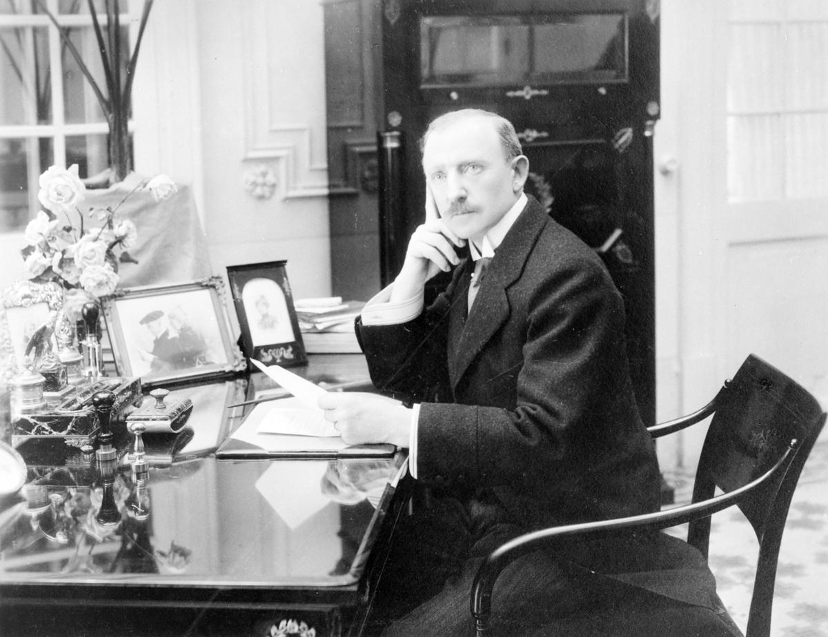 Mann sittende ved et bord. Minister Michael Strøm Lie. Sønn av dikter Jonas Lie.