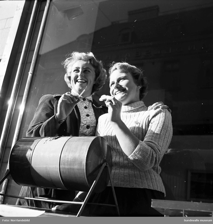 Två unga kvinnor med en tombola säljer Barnens Dagslotter på Storgatan 18.