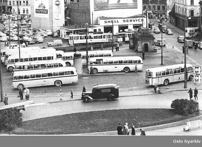 Oslo Sporveier. Sporveisbusser. Busser til bl.a. Østmarkruta ved buss-terminalen på Jernbanetorget. Shell bensinstasjon, trikk, gammel Vaterlandsbebyggelse. Parkeringsplass for biler. Helt til høyre svinger en trikk med Høkavogn inn i Vognmannsgata. Høkavognen kom først i drift 1953.