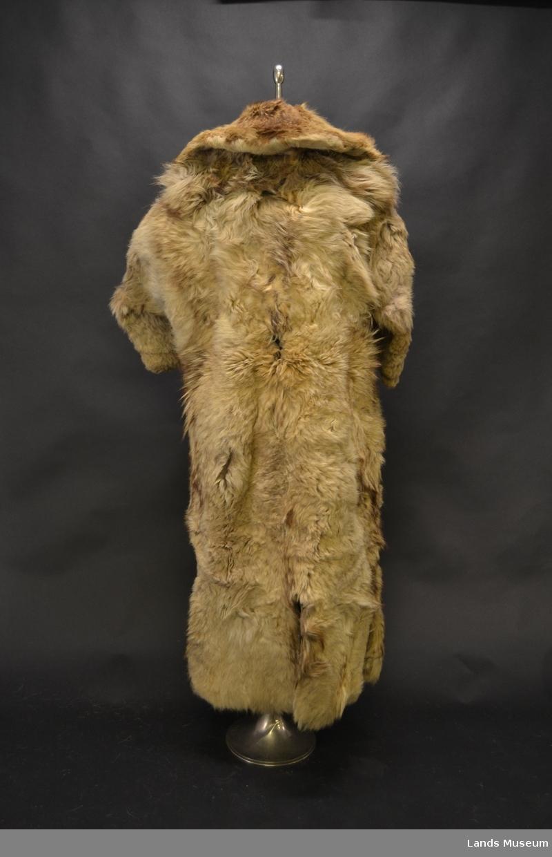 Foret med svart saueskinn, krave og oppbrett på armene i ulveskinn. Svart klede utvendig.