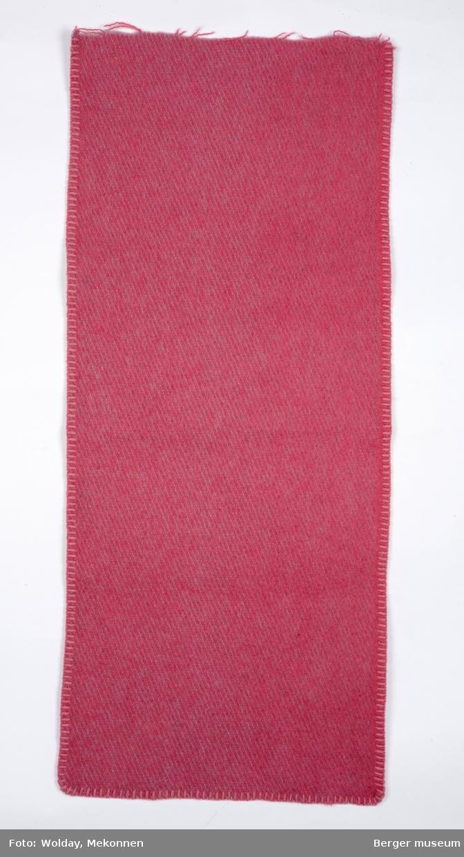 Et avlangt stykke pleddprøve, som er klippet av i ene enden, de andre sidene er sydd rundt. Teppet er to-farget, emd en farge på hver side.