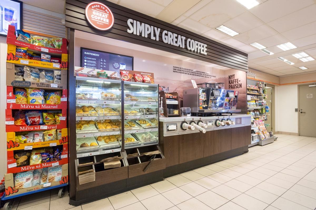 Statoil Nadderud. Butikk interiør med veggseksjon med kaffeautomat, engangsbegre, tilbehør til kaffe og ferske kaker og boller.