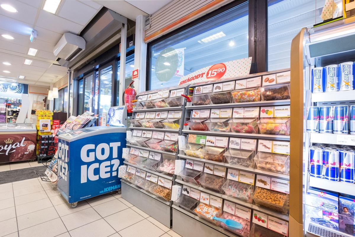 """Statoil Nadderud. Butikk inteiør med """"ta selv bokser"""" med godteri i løsvekt, Fryseboks i bakgrunnen."""