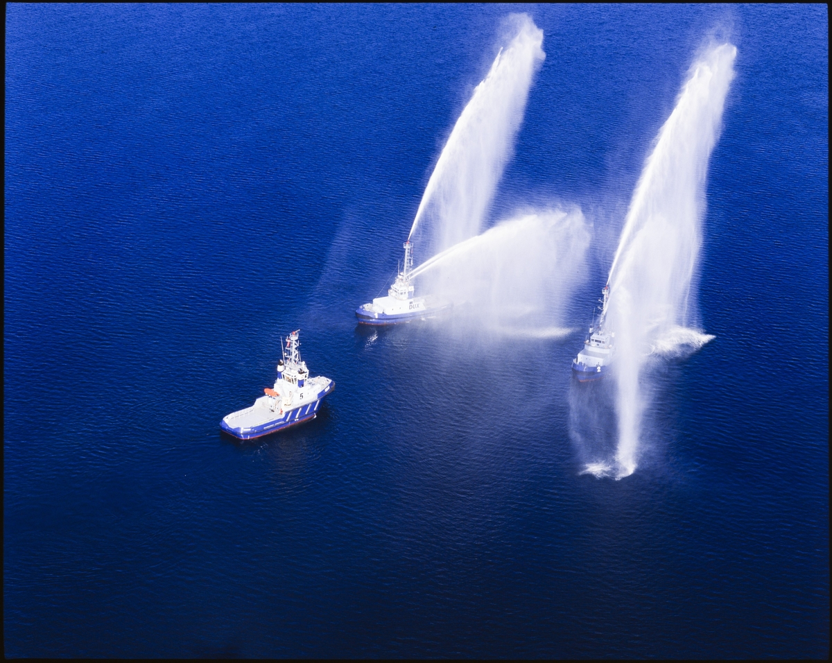To av tre taubåter spruter vann i ulike retninger på sjøen.