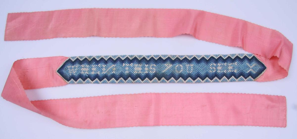 Av rosa silkerips uthakket langs kanten og smal fall for endene. På midten er påsydd en bord av fin, tett hekling i tre blåfarger og hvitt. Mønsteret består av langsgående sikk-sakkborder og en innskrift på midten.